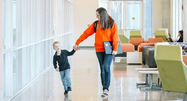 Online UTSA student walking with her child
